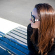 Royalty-Free Stock Photo: Young woman in sunglasses sitting at a wharf bench