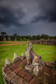 Stone carving of Angkor ruin with stormy sky — Stock Photo