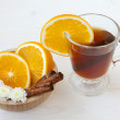 Cup of tea with orange and cinnamon sticks - Stock Photo