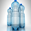Three bottles of water on reflection surface — Stock Photo