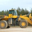 Heavy front loader in open pit - Stock Photo