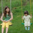 Stock Photo: Portrait of beautiful teenage and baby girls on swing