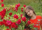 Portrait of beautiful teenage girl with dog rose flowers — Stock Photo
