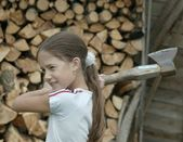 Portrait of teenage girl with lumber axe — Stock Photo