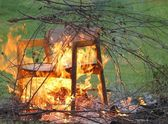 Burning branches and chair — Stock Photo