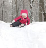 Portrait of smiling baby girl in snowdrift — Stock Photo