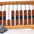 Photo: Old abacus with modern calculator isolated on white background