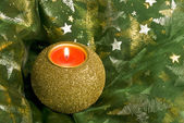Christmas Candle on Shiny Fabric with Glowing Stars — Stock Photo