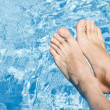Feet Over the Sparkling Pool - Stock Photo