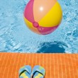 Beach Ball Floating in a Swimming Pool and Flip Flops — Stock Photo