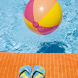 Beach Ball Floating in a Swimming Pool and Flip Flops — Stock Photo #12245687