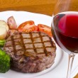 Barbecued Rib Eye Steak Served with Vegetables and a Glass of Red Wine - Stock Photo