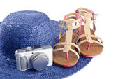 Pair of Woman Sandals resting on a Blue Straw Hat and a Small Digital Camera — Stock Photo