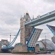 Stock Photo: Tower Bridge raises for The May a traditional Sail barge.