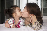 Mother kissing her daughter — Foto Stock