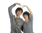 Romantic young couple making heart shape with arms — Stock Photo