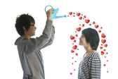 Romantic young couple pouring hearts from watering can — Stock Photo