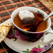 Cup of tea with pastry after dinner — Stock Photo