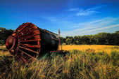 Old rusty rustic tower on its side in agricultural field — Stock Photo