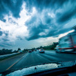 Stock Photo: Dramtatic sky and clouds with some rain while driving on highw