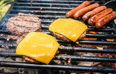 Hamburgers with cheese and hot dogs on grille — Stock Photo