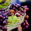 Grapes hanging out from crystal dish — Stock Photo