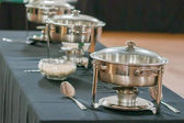 Banquet table with chafing dish heaters — Stock Photo