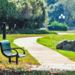 Bench in a park with a walkway — Stock Photo