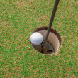 Foto de Stock  : Golf ball on green, in front of hole,