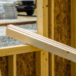 Stock Photo: Stack of wood stud planks at construction site resting on window