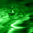 Green multi colored water drop bubbling — Stok fotoğraf