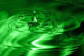 Green multi colored water drop bubbling — Stock Photo