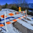 Road block set up before snowy and icy road in mountains — Stock fotografie