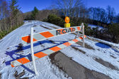 Road block set up before snowy and icy road in mountains — Stock Photo