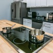 Kitchen butcher table island with stove top and pans — Stockfoto