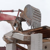 Wreck excavator at work demolishing a building wall — Stock Photo