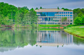 Office building reflecting in lake — Stock Photo