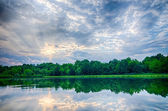 Sun setting over a reflective lake — Stock Photo