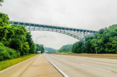 Steel bridge over highway on cloudy day in the mountains — Foto de Stock