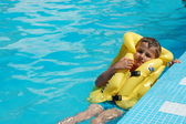 Boy in swimming pool wearing yellow life jacket — Stock Photo