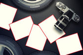 Blank card and vintage camera with car tire on carbon fiber background. — Stock Photo