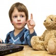 Boy teaches toy bear in front of laptop — Stock Photo #23501819