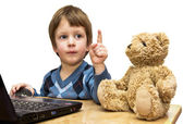The boy teaches a toy bear in front of the laptop — Stock Photo
