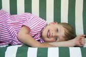 Cute three years boy lies on striped swing — Stock Photo