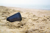 Mobile touch phone in sand on a beach — Stock Photo