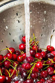 Cherry in colander under water — Stock Photo