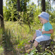 Cute three years boy in the forest on logs — Stock Photo