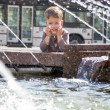 Boy near fountaine in summer day — Stock Photo