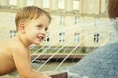 Boy near fountain in summer day — Stock Photo