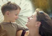 Mother and her little son outdoors in city near fountain — Stock Photo